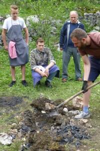 Der in Blätter gewickelte Hirsch wird ausgegraben. Kritisch beäugt von Philip Rachinger (knieend)